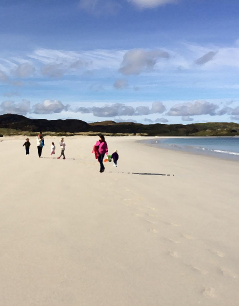 Image of family playing on beach in Western Isles
